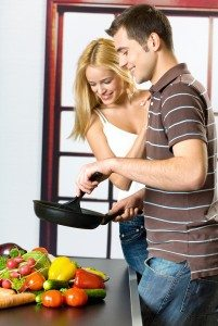 Young attractive happy smiling couple playfully cooking at kitch
