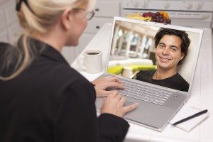 Happy Young Woman In Kitchen Using Laptop Online Dating Search with Portrait of Man On Screen.
