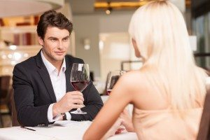 Attractive man with wine glass looking at beautiful woman.
