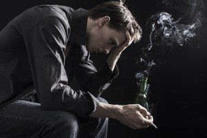Depressed smoking man sitting on chair on black background