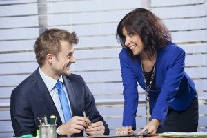 Smiling young business woman flirting with a man in the office