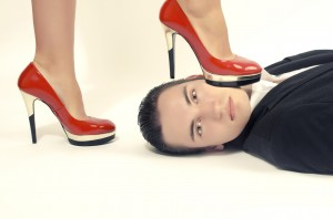 Woman in control of a man, sexy woman' foot on a man' face