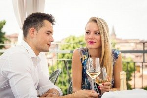 Attractive casual young couple drinking a glass of wine in a hot