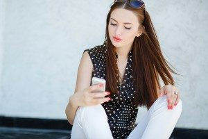 Young woman writes an SMS to your mobile phone