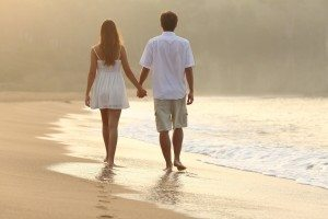 Couple walking and holding hands on the sand of a beach