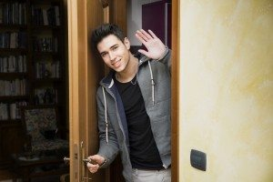 Smiling young man getting out of door waving at the camera