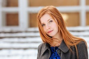 Closeup portrait of young beautiful redhead woman in blue dress and grey coat at winter outdoors