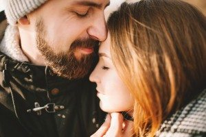 Close-up portrait of hipster couple hugging with closed eyes