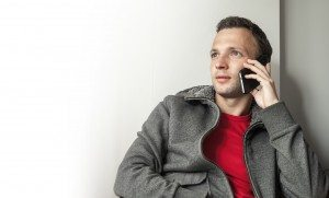 Portrait of young adult Caucasian man talking on mobile phone