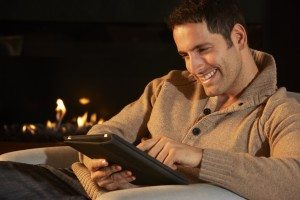 Man using tablet in front of fire at home
