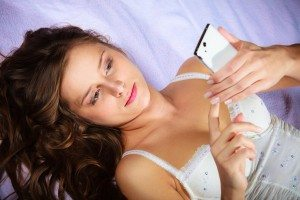 Lying girl holding smartphone.