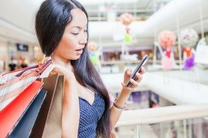 Fashion asian woman with bag using mobile phone, shopping center