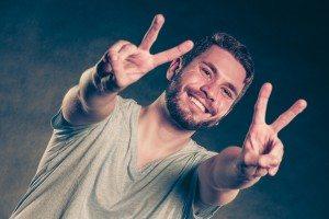 Handsome man guy giving peace v sign gesture.