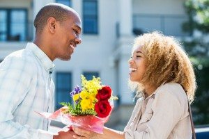 Young man gives flowers to girlfriend